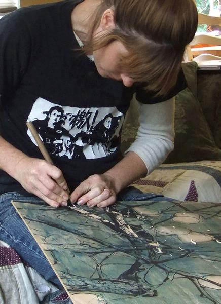 Sharon carving into the wood panel